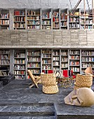 Bookcase in open-plan interior of concrete house