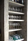 Neatly arranged glasses on concrete shelves