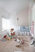 Girl playing with dolls' furniture in bedroom