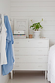Old white chest of drawers used as bedside table