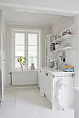 Küchenzeile in weißer Küche vor dem Fenster