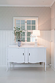Old sideboard against wainscoting and below interior window