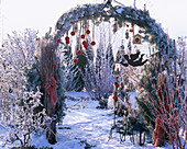 Rose arch in winter with red balls, tit dumplings, sheet metal ball and lanterns