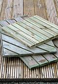 Various wooden tiles on floorboard