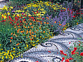 Mosaic path of Maggy Howarth through a colorful perennial border