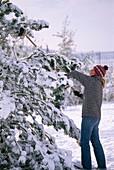 Junge Frau schüttelt Schneelast mit Besen