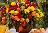 Bouquet made of pompondahlias, physalis, quinces (ornamental quince), ivy