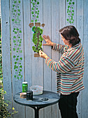 Painting a wooden wall with ivy using a stencil