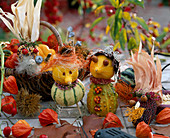 Figures are made from ornamental gourds and ornamental corn, rose hips as eyes, foliage cap