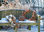 Garden bench in winter decorated with wreath of physalis