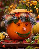 Pumpkin as a vase with face cucurbita squash, Tanacetum Tansy, Calocephalus