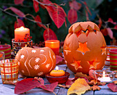 Cucurbita (pumpkin) eroded and decorated with star decoration, autumn leaves and candles