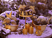 Advent decoration with snow and hoarfrost, cones, pine branch, gold balls, candles