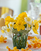 Small daffodils bouquet in glass vase with grass and bees decor