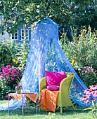 Green wicker armchair under blue mosquito net