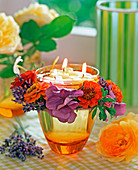 Glass with floating candles and Zinnia