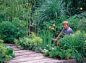 Boy near water basin with iris (marsh iris)