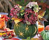 Cucurbita (pumpkin), hollowed out as a vase with bouquet