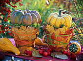 Cucurbita (pumpkin, ornamental squash) on clay pots, with autumn leaves