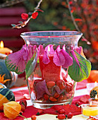 Glass wind light filled with pink (rose hip), brassica (ornamental cabbage)