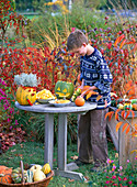 Boy making crafts with cucurbita (ornamental squash, pumpkin)