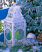 White lantern with ornaments and green candle in hoarfrost