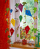 Paper kite and leaves on wire as window decoration, pink