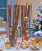 Glasses filled with cinnamon sticks, nuts and golden tree decorations, tableware