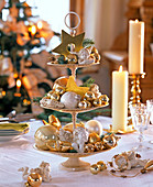 Beige metal etagere with golden and cream tree decorations