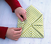 Fold green and white checkered cloth napkin