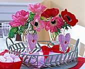 Anemone flowers in wine glasses, checkered fabric hearts