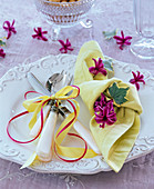 Knotted yellow napkin with flowers of Hyacinthus (hyacinth)