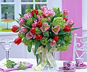Bouquet of tulipa (tulip) and viburnum (snowball) in glass vase