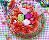 Easter basket with Dianthus flowers, Easter eggs, pink felt bunnies