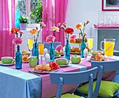 Breakfast table with dianthus in blue bottles, orange juice
