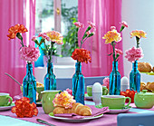Breakfast table with Dianthus (carnation) in blue bottles