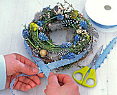 Easter wreath with grape hyacinths, feathers and eggs