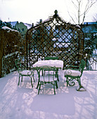 Snow-covered gray-green garnish in front of a covered metal arbor