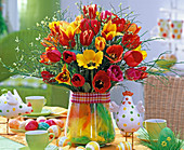 Tulip bouquet in vase with feathers