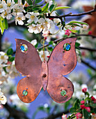 Flower shaped copper pendant on branch of malus (apple)