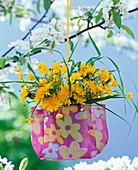 Taraxacum, ranunculus and grass in cloth bag