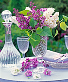 Purple and white syringa in tall glass vase, flowers, carafe, wine glass