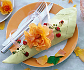 Rose with tendril of Fragaria on light green napkin