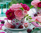 Rose flowers, light pink and red, in coffee cup with rose motif