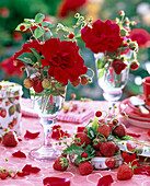 Pink (rose), Fragaria (strawberries) in glass and tin can