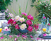Arrangement of paeonia and grasses on table runner made of hay