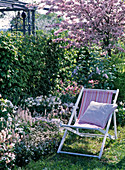 White bed in front of hedge, folding chair