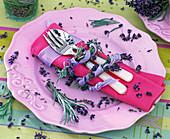 Lavandula as a napkin ring around pink napkin, cutlery