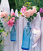 Roses, flowers and rose hips, clematis in blue bottles