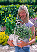 Woman with herbs in white handle basket